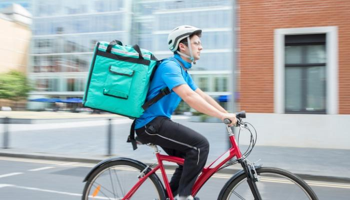 courier-on-bicycle-delivering-food-in-city-picture-id854337412