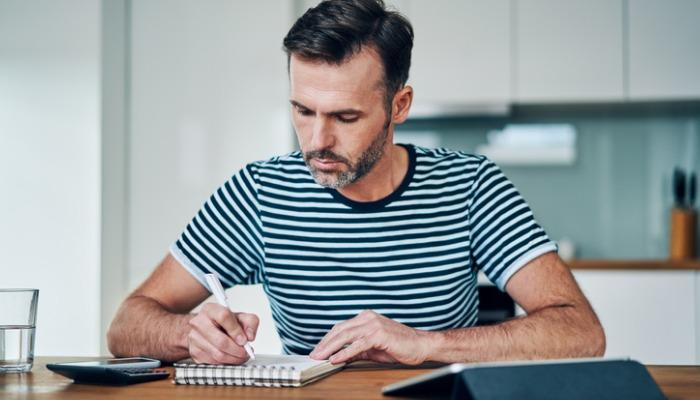 thoughtful-man-writing-in-notebook-while-managing-personal-budget-at-picture-id1217156777